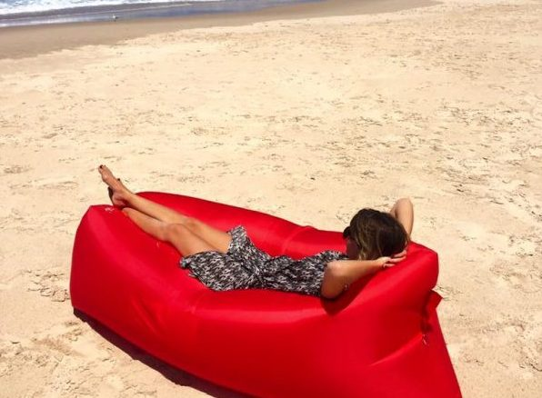person lying on their back in inflatable air lounge on the beach